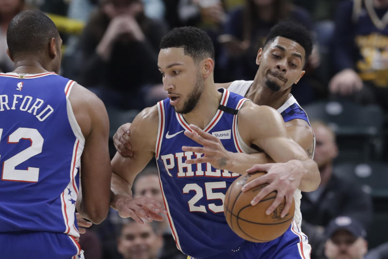 Philadelphia 76ers' Ben Simmons (25) is defended by Indiana Pacers' Jeremy Lamb (26) during the first half of an NBA basketball game, Monday, Jan. 13, 2020, in Indianapolis. (AP Photo/Darron Cummings)