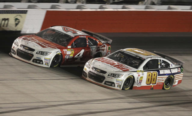 Kevin Harvick (4) passes Dale Earnhardt Jr (88) in Turn 4 on the next-to-last lap during the NASCAR Sprint Cup auto race at Darlington Raceway in Darlington, S.C., Saturday, April 12, 2014. Harvick won the race. (AP Photo/Chuck Burton)