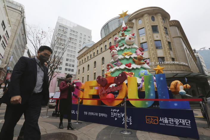 People wearing face masks to help protect against the spread of the coronavirus walk past a Christmas tree set up for a year-end festival featuring a lantern at a shopping street in Seoul, South Korea, Friday, Nov. 20, 2020. South Korea's prime minister has urged the public to avoid social gatherings and stay at home as much as possible as the country registered more than 300 new virus cases for a third consecutive day. (AP Photo/Ahn Young-joon)