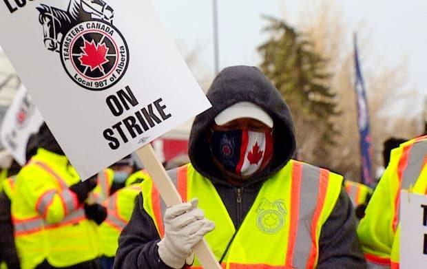 Employees walk the picket line at the Coca-Cola facility in northeast Calgary on Monday.  (Mike Symington/CBC - image credit)