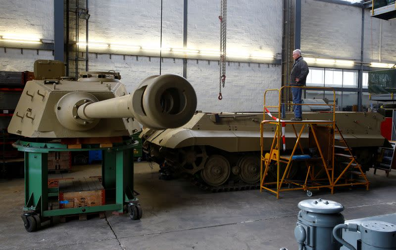 "Kubicki stands beside the hull of a German World War II Tiger II ""King Tiger"" tank during restoration works at Swiss Military Museum Full in Full"