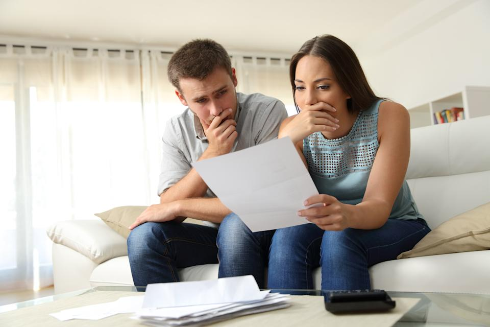 Worried couple reading a letter sitting on a couch in the living room at home