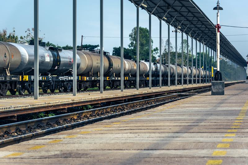A line of tanker cars in front of a rail station.