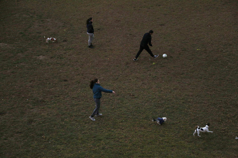 People play with their dogs and a ball at a park in Famagusta gate in central capital Nicosia, Cyprus, Wednesday, Jan. 27, 2021. Cyprus' health minister Constantinos Ioannou said that the first to re-open as of Feb. 1st will be hair and beauty salons followed a week later by retail stores, shopping malls and elementary schools. Students in their final year of high school will also go back to classes on Feb. 8. (AP Photo/Petros Karadjias)