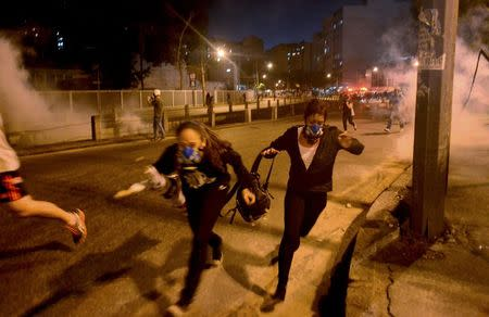 Protesters run from tear gas shot by riot police in Rio de Janeiro