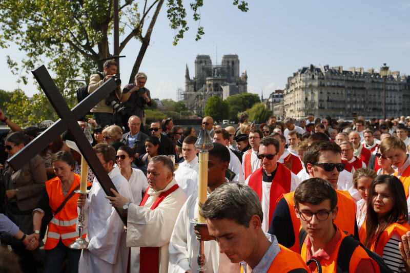 Religious officials carry the cross during a Good Friday procession in Paris on April 19, 2019. (Francois Mori / ASSOCIATED PRESS)