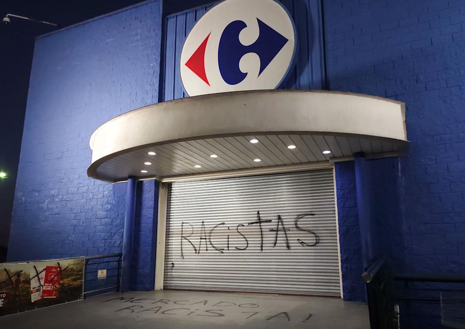 """A graffiti written by demonstrators reads """"Racists"""" at the entrance of a Carrefour supermarket in Curitiba, Brazil, on November 20, 2020. - The death of a black man on Thursday night after being beaten by white security agents in a supermarket belonging to the Carrefour group in Porto Alegre unleashed a wave of indignation in Brazil. (Photo by Guilherme BITTAR / AFP) (Photo by GUILHERME BITTAR/AFP via Getty Images)"""
