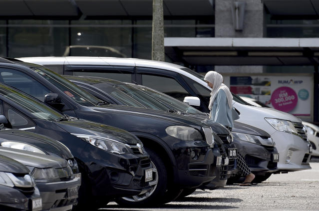 A woman walks toward her car in a parking lot in Putrajaya, Malaysia, Wednesday, Jan. 16, 2019. An automotive group says vehicle sales in Malaysia last year has rebounded after two years of consecutive contraction thanks to a three-month tax holiday but growth is likely to remain flat this year amid uncertainties over government policies. (AP Photo/Yam G-Jun)