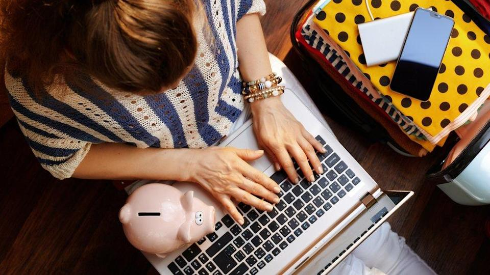 Woman with computer and piggy bank