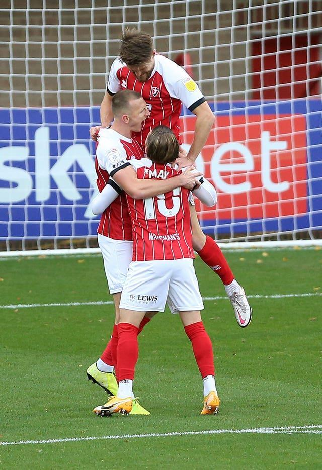 Cheltenham's Will Boyle (centre) with Alfie May (bottom) and Charlie Raglan (top) celebrate taking the lead against Premier League Manchester City Bet League Two – Jonny-Rocks Stadium