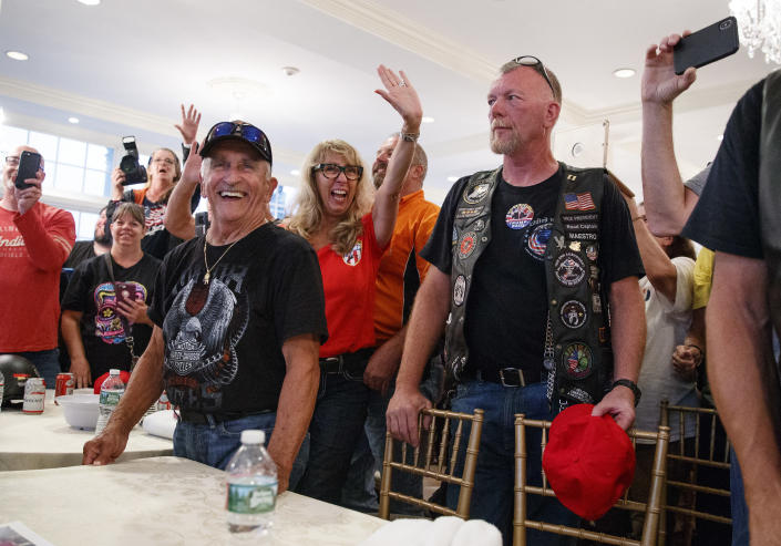 Supporters and members of Bikers for Trump wave and cheer, Saturday, Aug. 11, 2018, in the ballroom of Trump National Golf Club in Bedminster, N.J, during a meeting with President Donald Trump. (AP Photo/Carolyn Kaster)