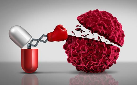 Pill opened up with boxing glove on end of mechanical arm punching cancer cell