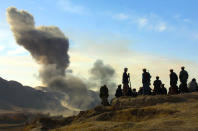 FILE - In this Nov. 19, 2001 file photo, Northern Alliance soldiers watch as U.S. air strikes attack Taliban positions in Kunduz province, Afghanistan. (AP Photo/Ivan Sekretarev, File)