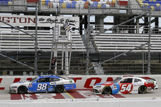 Chase Briscoe (98) crosses the finish line ahead of Kyle Busch (54) to win the NASCAR Xfinity series auto race Thursday, May 21, 2020, in Darlington, S.C. (AP Photo/Brynn Anderson)