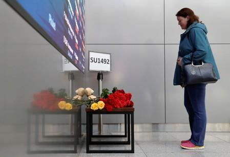 FILE PHOTO: A woman commemorates victims of an incident involving an Aeroflot Sukhoi Superjet 100 passenger plane at Moscow's Sheremetyevo airport