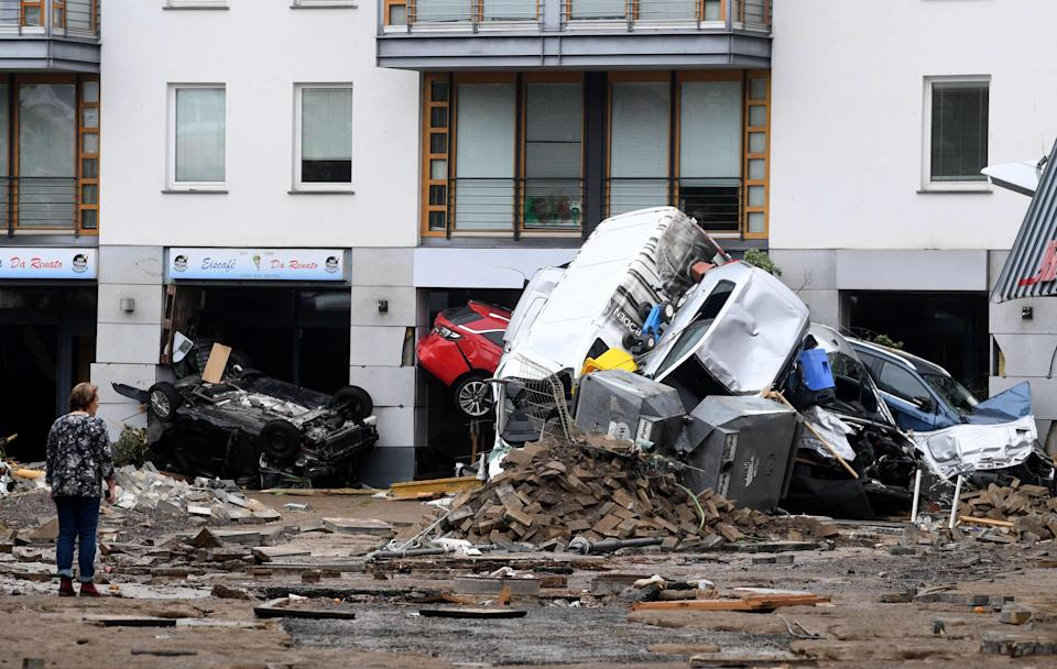 A woman looks at cars and rubble piled up in a street after the floods caused major damage in Bad Neuenahr-Ahrweiler, western Germany (AFP via Getty Images)