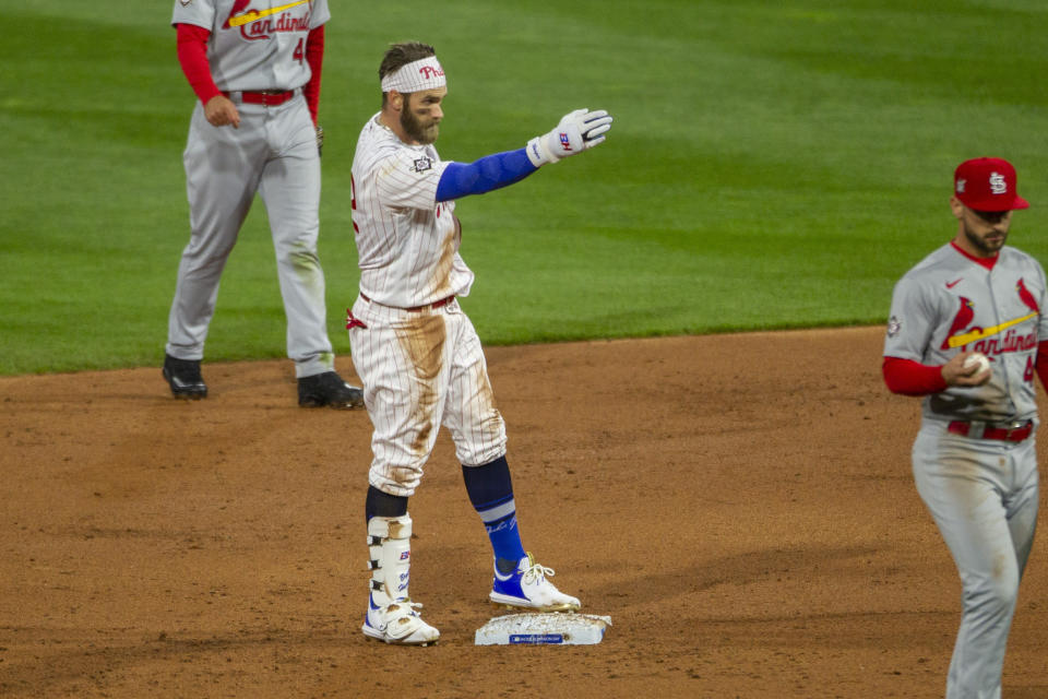 Philadelphia Phillies' Bryce Harper gestures from second base to the team's dugout after hitting an RBI double during the second inning of a baseball game against the St. Louis Cardinals, Friday, April 16, 2021, in Philadelphia. (AP Photo/Laurence Kesterson)