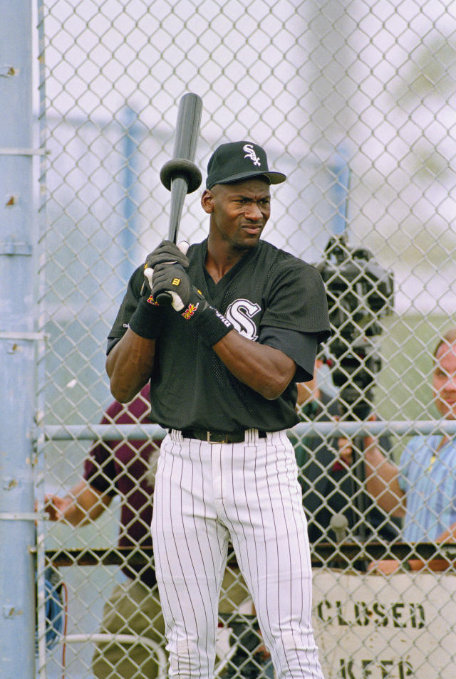 Michael Jordan swings a weighted bat while waiting for his turn in the batting cage during his first day of spring training with the Chicago White Sox, in Sarasota, Feb. 2, 1994. (AP Photo/John Swart)