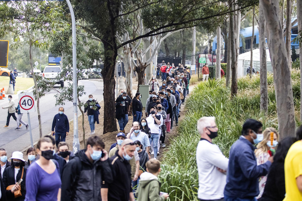 SYDNEY, AUSTRALIA - JULY 01: Long queues of people are seen at the NSW Vaccination Centre in Homebush on July 01, 2021 in Sydney, Australia. Much of Australia is in lockdown or subject to some form of restriction as community cases of the COVID-19 Delta variant continue to be recorded around Australia. Currently, the Pfizer vaccine is available to frontline workers, people with pre-existing health conditions and people in their 40s and 50s, while the AstraZeneca vaccine is recommended for people over 60. Prime Minister Scott Morrison on Monday announced an indemnity scheme for general practitioners, saying anyone could receive AstraZeneca at a GP clinic despite vaccine advisory group ATAGI recommending Pfizer as the preferred vaccine for those under 60. (Photo by Jenny Evans/Getty Images)