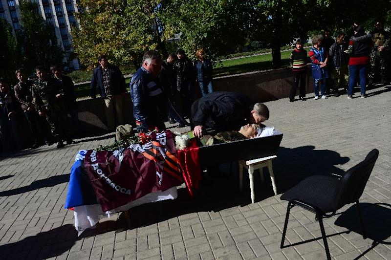 People pay respects as body of pro-Russian separatist Konstantin Dobriden, of the Berkut Battalion, lies in state during a ceremony outside the headquarters of the self-Proclaimed People's Republic of Donetsk, eastern Ukraine, on October 3, 2014 (AFP Photo/John Macdougall)