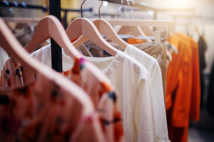 Various shirts and blouses hanging on a rack in a store.