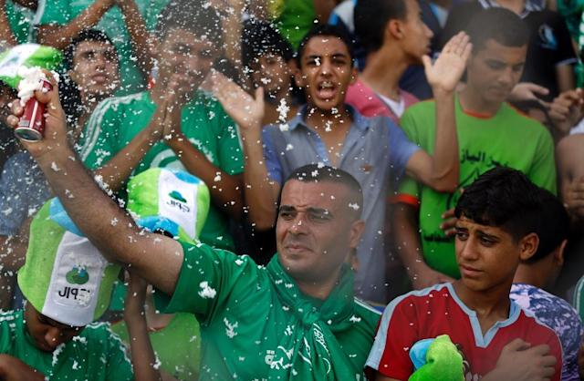 Palestinian spectators cheer during a football match between the West Bank-based Al-Ahli and Gaza's Shejaiya, playing each other for the first time in 15 years, at the al-Yarmuk stadium in Gaza City on August 6, 2015 (AFP Photo/Mohammed Abed)