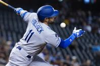 Los Angeles Dodgers' AJ Pollock fouls a ball off his face during the first inning of a baseball game against the Arizona Diamondbacks Sunday, Sept. 26, 2021, in Phoenix. (AP Photo/Ross D. Franklin)