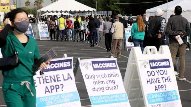 PHOTO: A line of to receive the COVID-19 vaccine at a mass vaccination site strethes into a parking lot for Disneyland Resort in Anaheim, Calif., on Jan. 13, 2021. (Mario Tama/Getty Images)