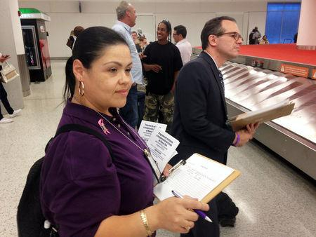 Emily Pagan, a New York state government official, greets and help orients people arriving from Puerto Rico and the U.S. Virgin Islands at John F. Kennedy International Airport in New York, U.S. October 19, 2017.  Photo taken October 19, 2017.   REUTERS/Jonathan Allen