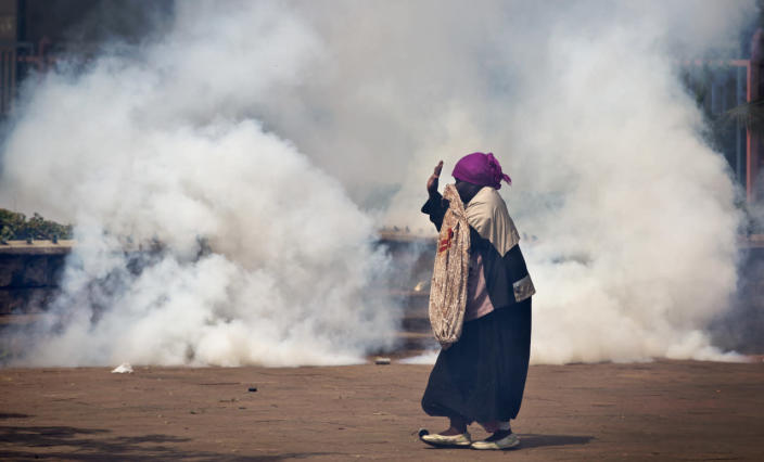 An elderly woman caught up in the clashes holds her hands in the air as a riot policeman approach amidst clouds of tear gas, during a protest in downtown Nairobi, Kenya, May 16, 2016. Kenyan police have tear-gassed and beaten opposition supporters during a protest demanding the disbandment of the electoral authority over alleged bias and corruption. (AP Photo/Ben Curtis)
