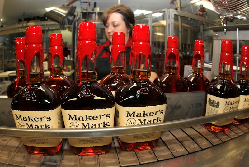New bottles of Maker's Mark bourbon on the conveyor belt pass by a worker after being hand dipped with their signature red wax, on their way to packaging at the Maker's Mark Distillery plant in Loretto, Kentucky January 23, 2014.