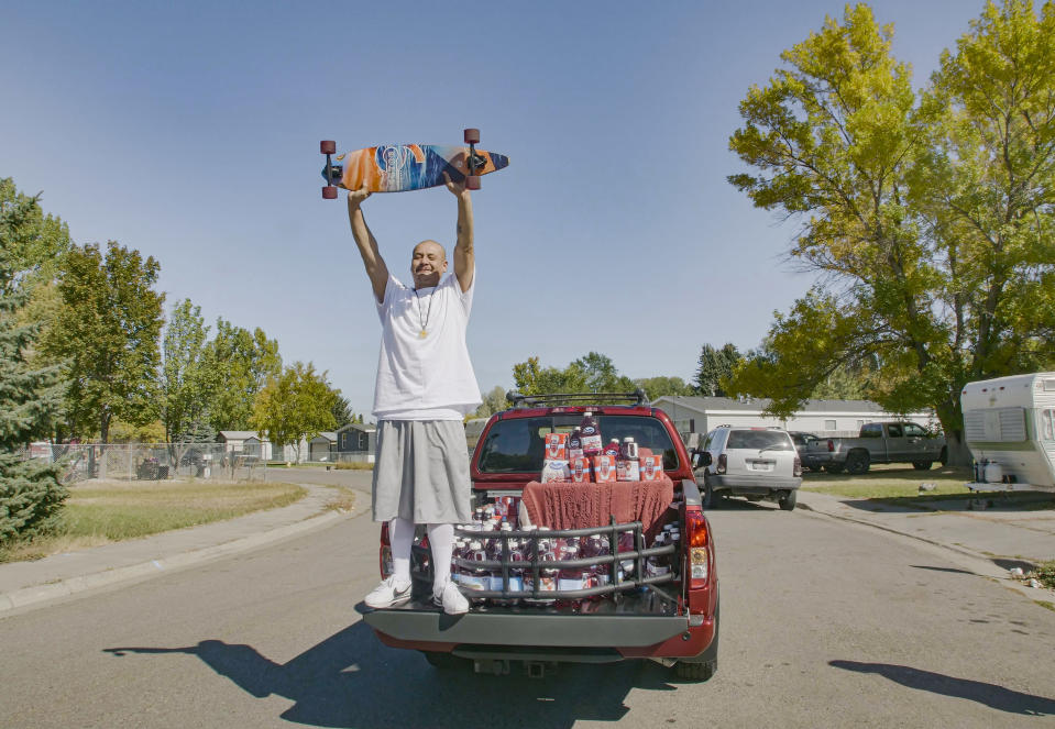 "This Oct. 6, 2020 photo released by Ocean Spray shows Nathan Apodaca holding his skateboard while standing in the back of a truck with Ocean Spray products in Idaho Falls, Idaho. Apodaca is enjoying fame from a 22-second TikTok video in which he chugs cranberry juice and sings along to Fleetwood Mac's ""Dreams"" while cruising down an Idaho highway atop a longboard. The video has racked up 28 million views and counting since he posted it last month. Ocean Spray, whose juice Apodaca is seen swigging in the video, gave him a new truck stocked with juice this week. (Wesley White/Ocean Spray via AP)"
