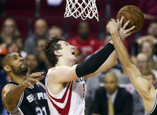 Houston Rockets center Omer Asik (3) drives to the basket past San Antonio Spurs forward Tim Duncan (21) during the first half of an NBA basketball game, Sunday March, 24, 2013, in Houston. (AP Photo/Patric Schneider)