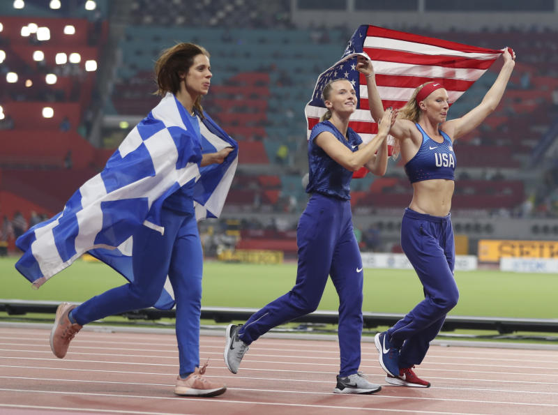 Anzhelika Sidorova, center, competing as a neutral athlete, celebrates with Katerina Stefanidi, left, competing as a neutral athlete; and Sandi Morris, right, of the United States; after the women's pole vault final at the World Athletics Championships in Doha, Qatar, Sunday, Sept. 29, 2019. Sidorova won the gold medal, Morris won the silver and Stefanidi won the bronze. (AP Photo/Hassan Ammar)
