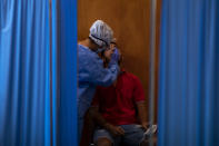 A Spanish NGO Open Arms volunteer takes a swab to test a man for COVID-19, at Vilafranca del Penedes in the Barcelona province, Spain, Tuesday, Aug. 11, 2020. Spain is facing another surge in coronavirus infections not even two months after beating back the first wave. (AP Photo/Emilio Morenatti)