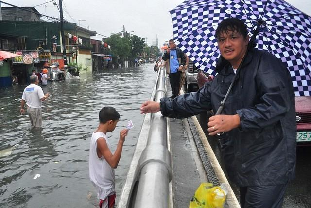 Business as usual. A man takes advantage of the situation and sells various products such as coffee, bread and cigarettes to stranded commuters. Majority of the metro is flooded due to heavy rains from the previous night, seen at Lacson Avenue in Sampaloc, Manila on 07 August 2012. (George Calvelo, NPPA Images)