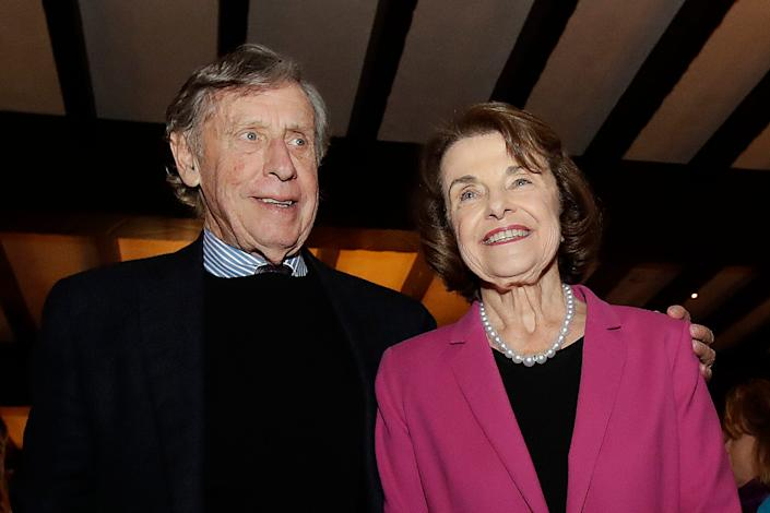 FILE - In this Nov. 6, 2018, file photo, U.S. Sen. Dianne Feinstein, right, smiles next to husband Richard Blum at an election night event in San Francisco.
