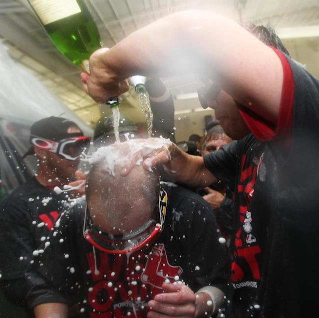 Boston Red Sox second baseman Dustin Pedroia is doused with sparkling winde as he celebrates with teammates after the Red Sox clinched the AL East title with a 6-3 win over the Toronto Blue Jays in a baseball game at Fenway Park, Friday, Sept. 20, 2013, in Boston. (AP Photo/Charles Krupa)