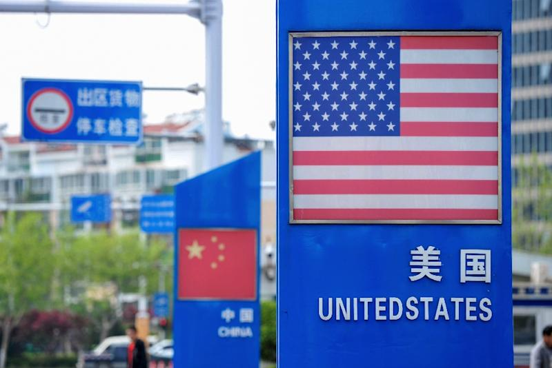 Signs with the US and Chinese flags are displayed in Qingdao free trade port area of Qingdao, in China's eastern Shandong province, ahead of UE President Donald Trump's plan to raise tariffs on $200 billion in Chinese goods (AFP Photo/STR)