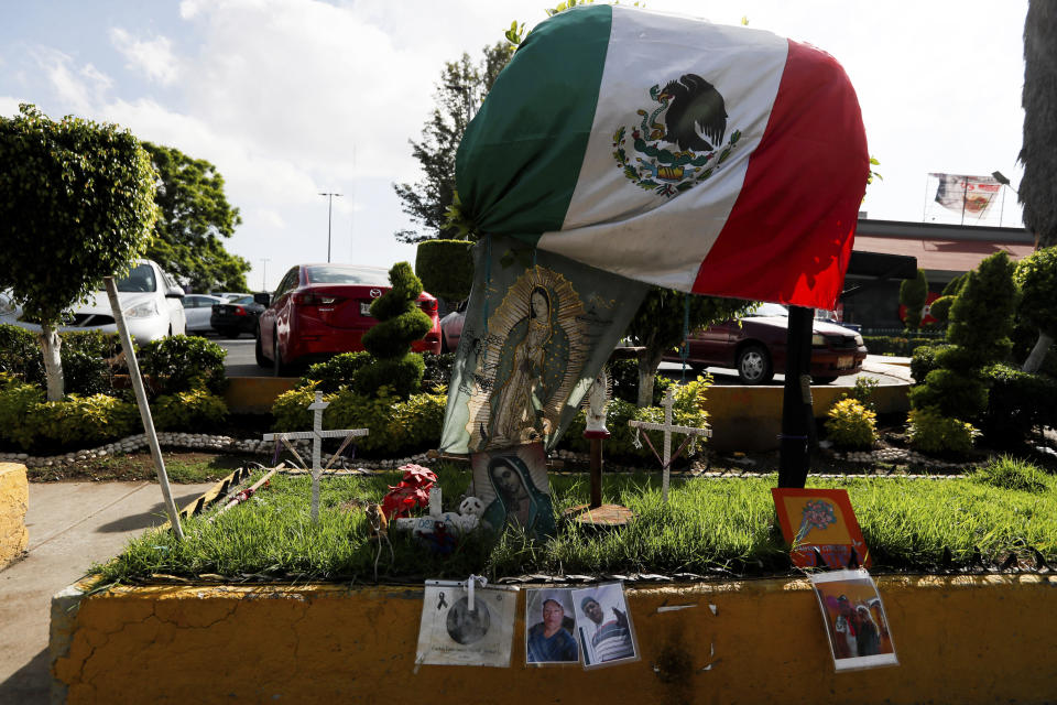 Photos of people who died in a metro collapse hang alongside a Mexican flag and images of Our Lady of Guadalupe, at the site of the now missing metro section in Mexico City, Wednesday, June 16, 2021. A June 16, 2021 preliminary report by experts into the collapse that killed 26 people placed much of the blame on poor welds in studs that joined steel support beams to a concrete layer supporting the trackbed. (AP Photo/Fernando Llano)