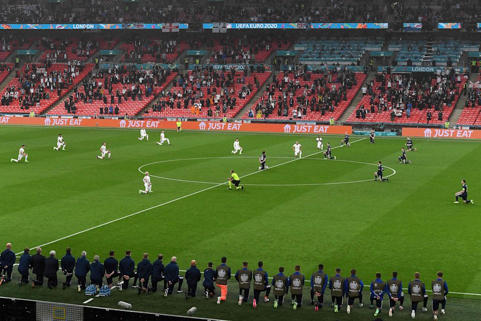 Players kneel down before the match (AFP/Getty)