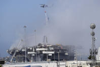 A helicopter drops water on the USS Bonhomme Richard, Monday, July 13, 2020, in San Diego. Fire crews continue to battle the blaze Monday after 21 people suffered minor injuries in an explosion and fire Sunday on board the USS Bonhomme Richard at Naval Base San Diego. (AP Photo/Gregory Bull)
