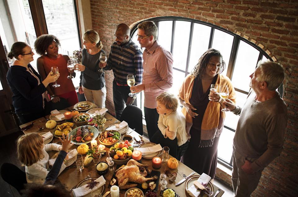 adults and children gather around a thanksgiving table inside
