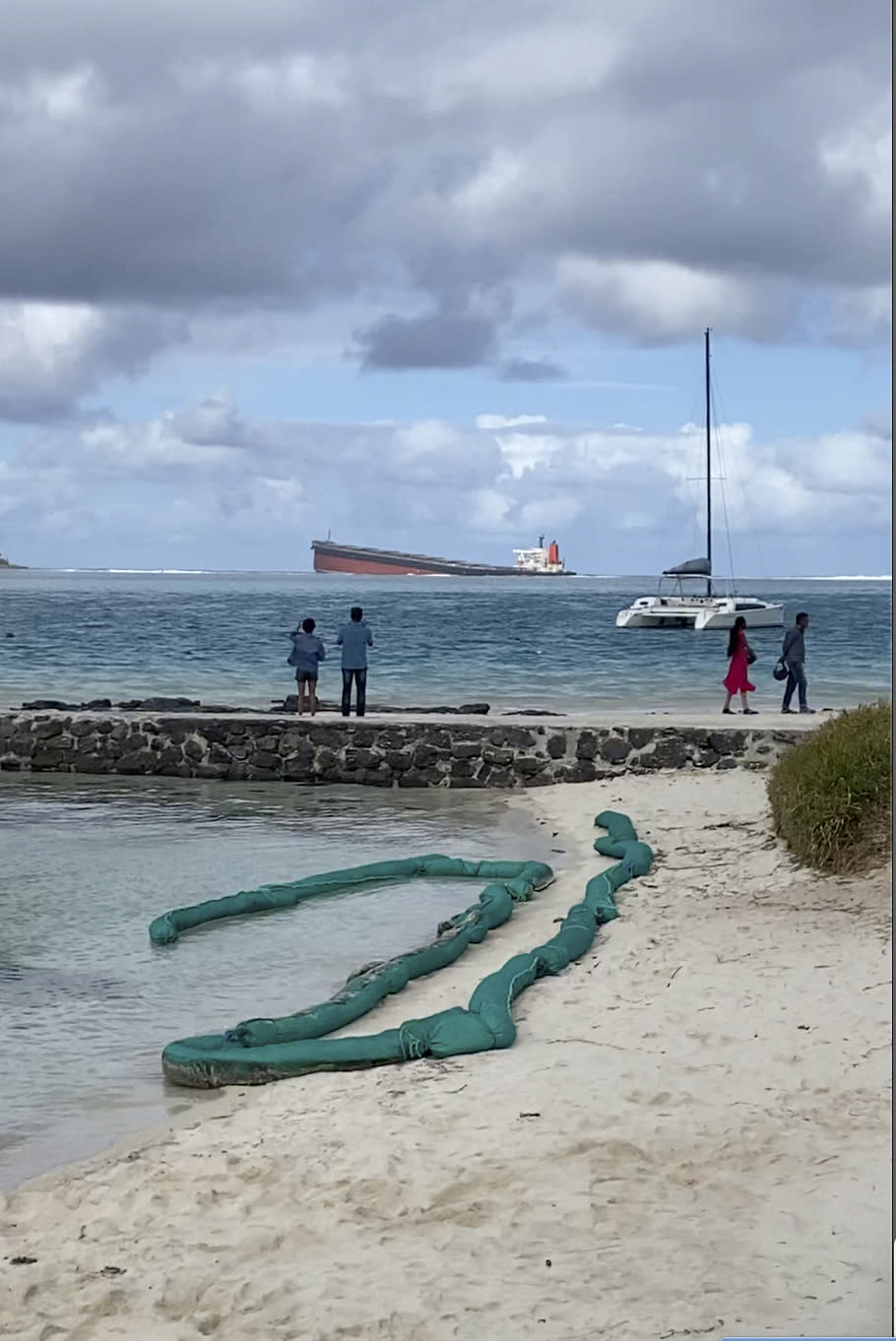 """In this still image taken from video provided by Grégoire Rouxel, people watch a ship that ran aground offshore that is leaking fuel, Friday, Aug. 7, 2020, in Mauritius. The Indian Ocean island of Mauritius has declared a """"state of environmental emergency"""" after a Japanese-owned ship that ran aground offshore days ago began spilling tons of fuel. Prime Minister Pravind Jugnauth announced the development late Friday, as satellite images showed a dark slick spreading near environmental areas the government called """"very sensitive."""" (@gregrouxel via AP)"""