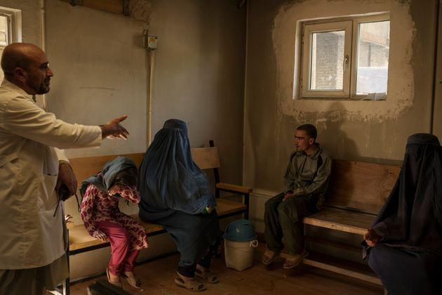 Dr. Wahedullah Koshan, left, gestures as he talks to Sitara, center, after she reunited with her 21-year-old son who was taken to the Avicenna Medical Hospital for Drug Treatment during a Taliban raid in Kabul, Afghanistan, Monday, Oct. 4, 2021. Sitara wails when she reunited with her son, missing for 12 days.