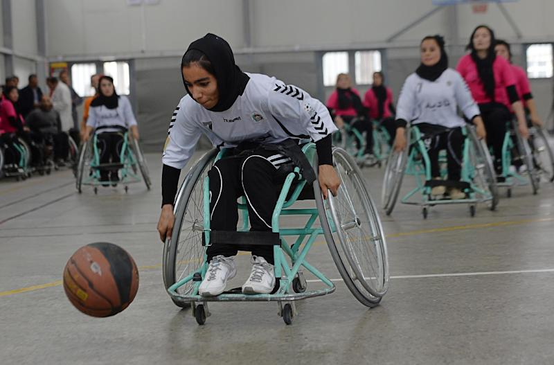 An Afghan member of the Mazar-i-Sharif wheelchair basketball team plays against the team from Kabul during the final of the country's third annual competition in Kabul on October 29, 2014