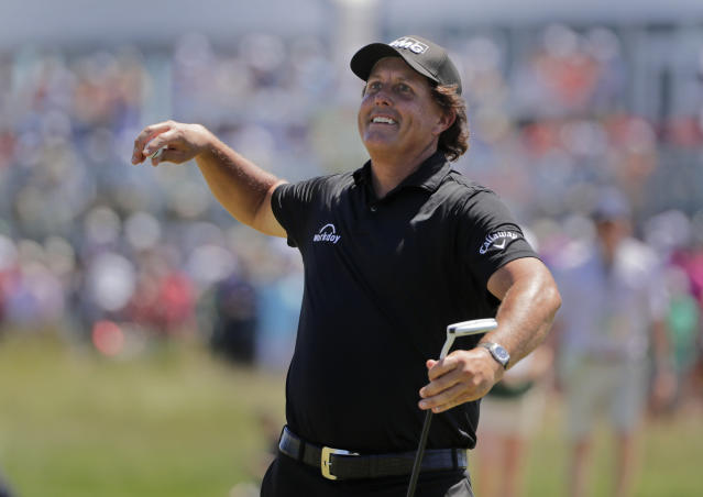 Phil Mickelson throws his ball into the crowd after sinking a putt on the 13th hole during the final round of the U.S. Open Golf Championship, Sunday, June 17, 2018, in Southampton, N.Y. (AP Photo/Frank Franklin II)