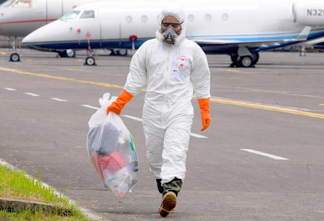An officer wears protective gear while handling waste at an air-force base in Jakarta. (Getty Images)