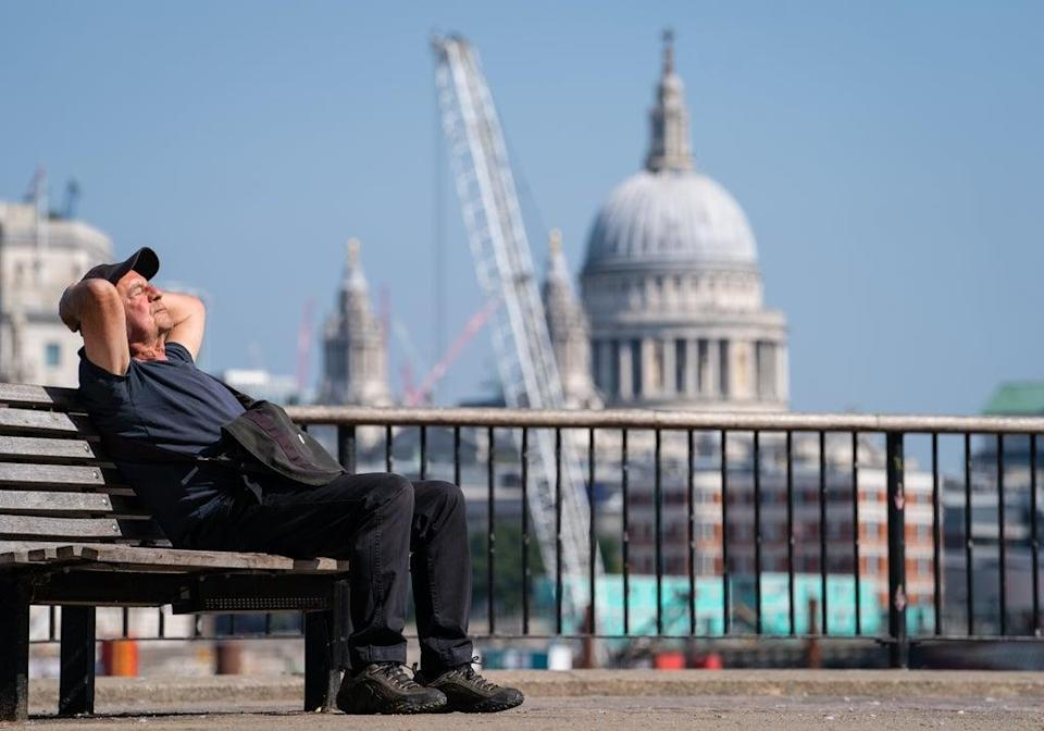 A man soaks up the sun within sight of St Paul's Cathedral on the South Bank, London (Dominic Lipinski/PA) (PA Wire)