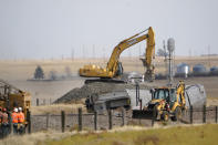 Heavy equipment moves gravel Sunday, Sept. 26, 2021, next to cars from an an Amtrak train that derailed Saturday just west of Joplin, Mont. The westbound Empire Builder was en route to Seattle from Chicago, with two locomotives and 10 cars. (AP Photo/Ted S. Warren)